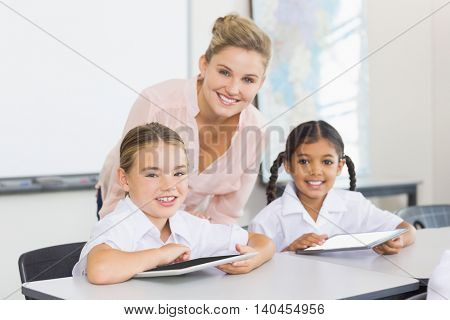 Teacher and kids using digital tablet in classroom at school
