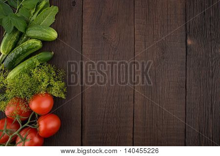 Tomatoes cucumbers dill and horseradish leaves on the old wooden background. Top view.