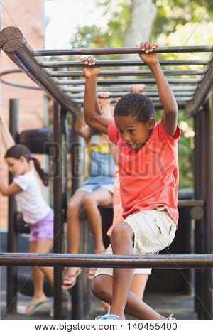 Schoolboy hanging on monkey rack at playground