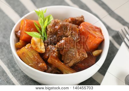 Stewed beef with carrot garlic and herbs in white bowl on the table