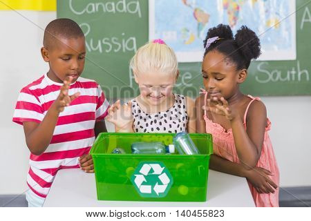 School kids looking recycle logo box in classroom at school