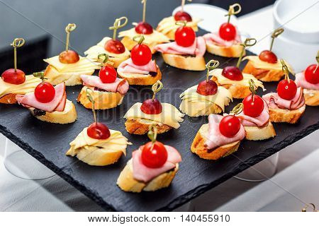Small crostini with grilled baguette, cherry tomatoes, ham slices, cheese and fresh grapes on black background. Sandwiches or assorted canapes on a dark board, top view.