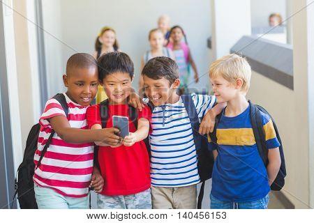 School kids taking selfie on mobile phone in corridor at school