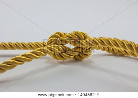Small gold rope leads to tie or bundle.