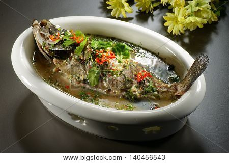Special braised grouper fish with soup in chinese style in white big bowl on the table in restaurant