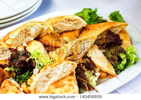 Beautifully decorated catering banquet table with different food snacks and appetizers with sandwich, pancakes, fresh salad on corporate christmas birthday party event or wedding celebration.
