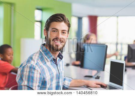 Teacher using laptop in classroom at school