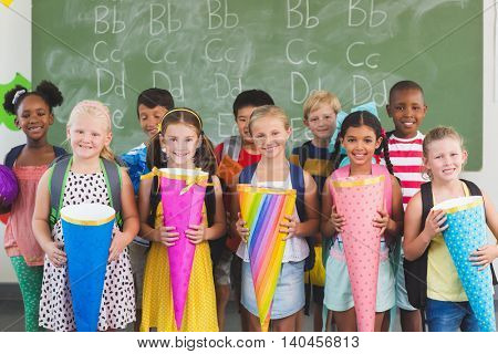 Portrait of happy kids holding gifts in classroom at school