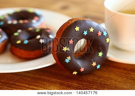 Donut of cake with chocolate and sugar stars on the table with tea cup