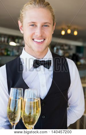 Portrait of waiter holding glasses of champagne in restaurant