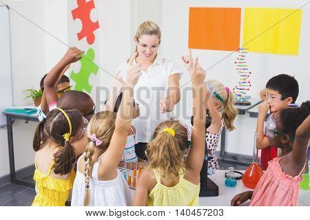 Kids raising hand in laboratory at school