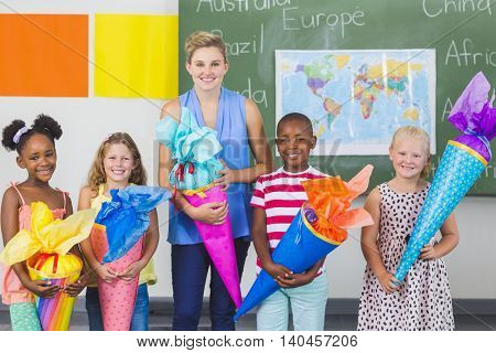 Happy kids and teacher holding gifts in classroom at school