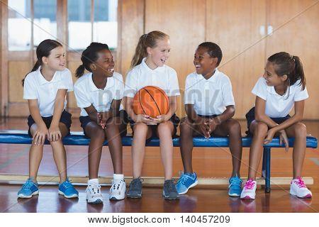 School kids having fun in basketball court at school