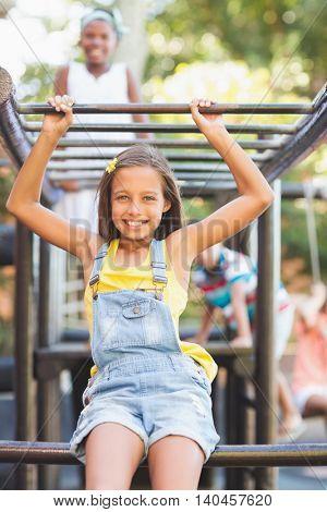 Happy schoolgirl sitting on monkey rack at playground