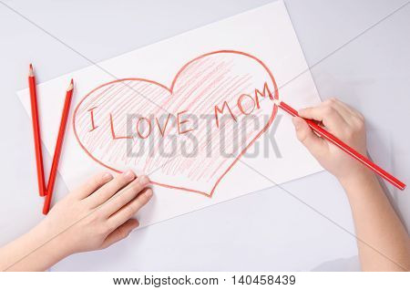 Childs Hands Drawing A Heart That Says I Love Mom
