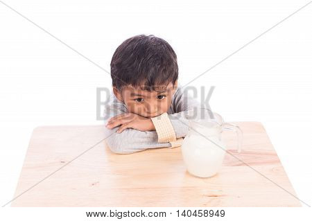 Cute little boy bored with milk on white background