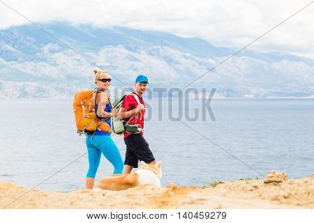 Happy couple hikers trekking with akita dog in summer mountains at seaside. Young woman and man walking on rocky mountain trail path looking at beautiful inspirational landscape view.