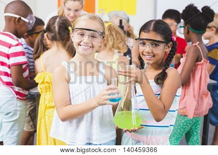 Portrait of kids holding laboratory flask in laboratory at school