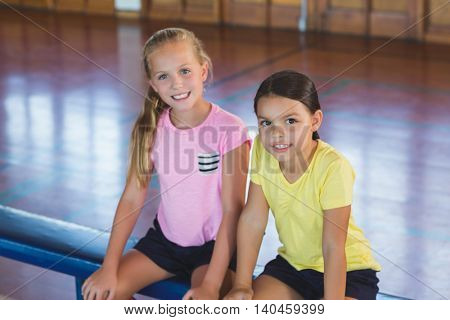 Portrait of girls sitting on bench in basketball court at school gym