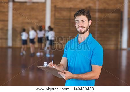 Portrait of sports teacher writing on clipboard in basketball court at school gym