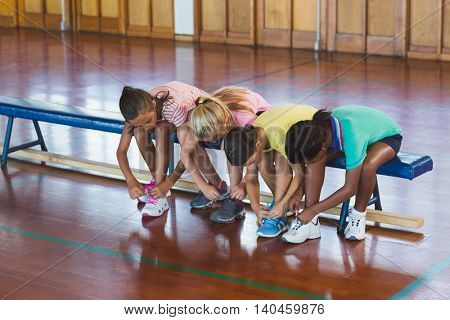 Girls tying shoe laces in basketball court at school gym