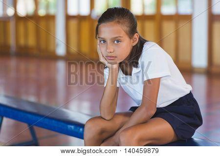 Portrait of schoolgirl sitting in basketball court at school gym