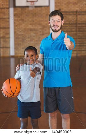 Portrait of sports teacher and schoolboy showing thumbs up in basketball court at school gym