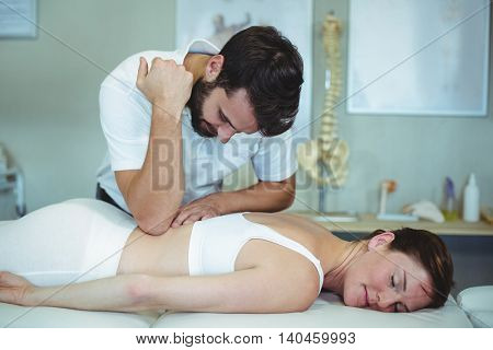 Physiotherapist giving back massage to a woman in clinic