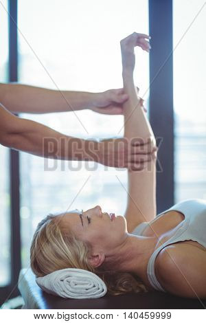 Woman receiving hand therapy exercises from physiotherapist in clinic