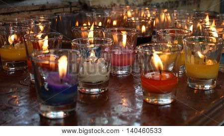 Church candles in red and yellow transparent chandeliers