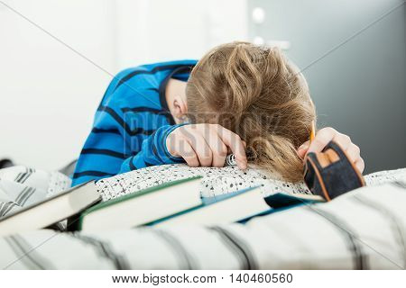 Exhausted Young Boy Asleep On His Text Books