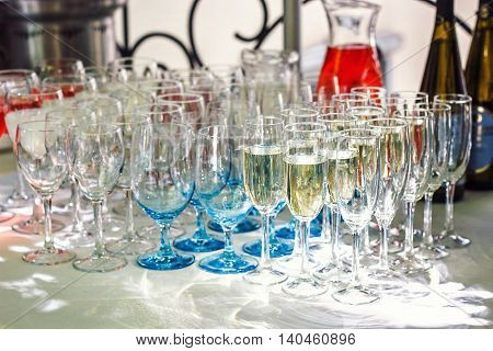 Beautiful row line of different glasses filled with champagne are lined up ready to be served on a christmas party, martini, vodka,and others on decorated catering bouquet table on open air event.