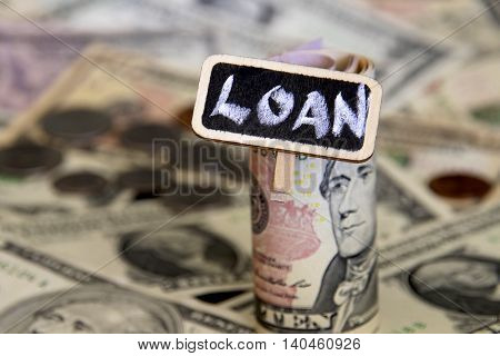 Loan sign with a background of American dollars.