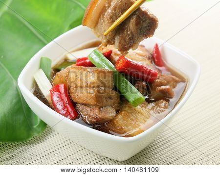 Cane fragrant braised pork with chili and onion in white pot on bamboo tray