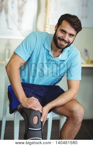 Portrait of smiling man with knee injury in clinic