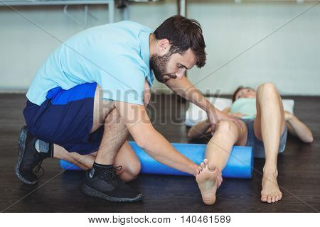 Physiotherapist doing leg therapy to a woman using foam roll in clinic