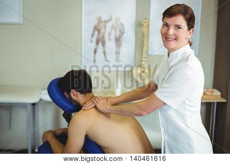 Portrait of physiotherapist giving back massage to a patient in the clinic