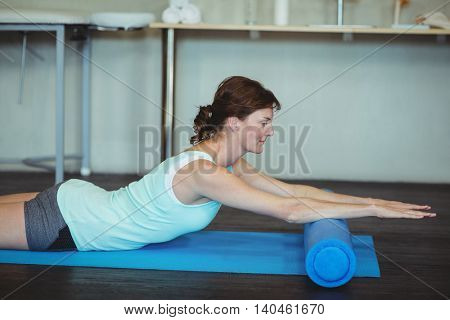 Woman performing stretching exercise on mat in clinic