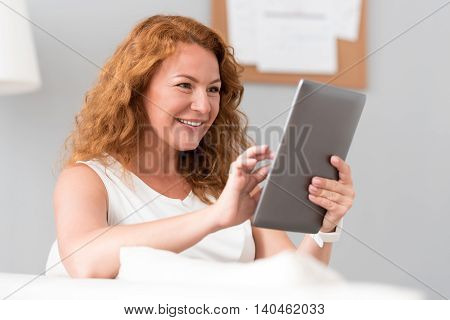 Rest at home. Cheerful beautiful senior woman sitting on the couch and using tablet while resting at home