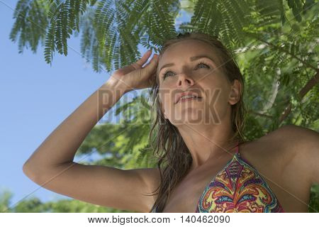 Closeup of pretty blonde woman wearing colourful swimwear on a beautiful summer day over tree and sky background