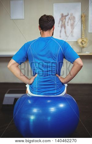 Man sitting on exercise ball in the clinic