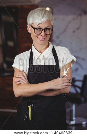 Portrait of female hairdresser standing with arm crossed at a salon