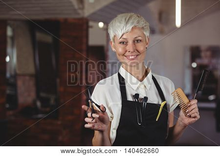 Portrait of female hairdresser standing scissor and comb at a salon