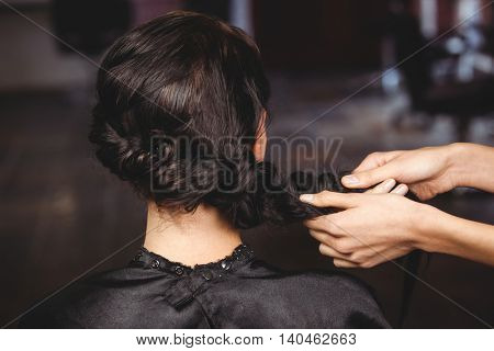 Female hairdresser styling customers hair at a salon