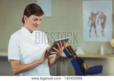 Physiotherapist using digital tablet in clinic