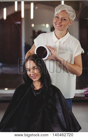 Portrait of hairdresser showing woman her haircut in mirror at salon