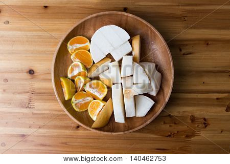 Sliced orange and pear on wooden plate and table