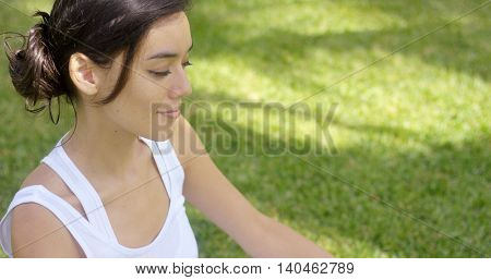 Serene young woman meditating on a green lawn