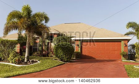 Typical Southwest Florida concrete block and stucco home in the countryside with palm trees tropical plants and flowers grass lawn and pine trees. Florida