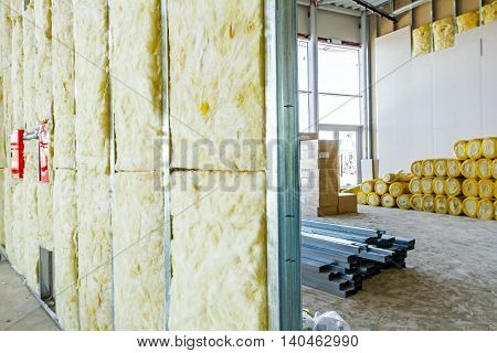 Unfinished building interior heat isolation wall project with mineral wool is in progress.